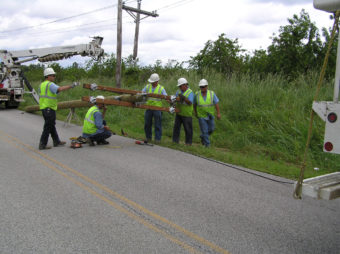 Linemen working on a downed power pole on a road.