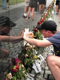 Boy writing on paper at the Vietnam Veterans Memorial