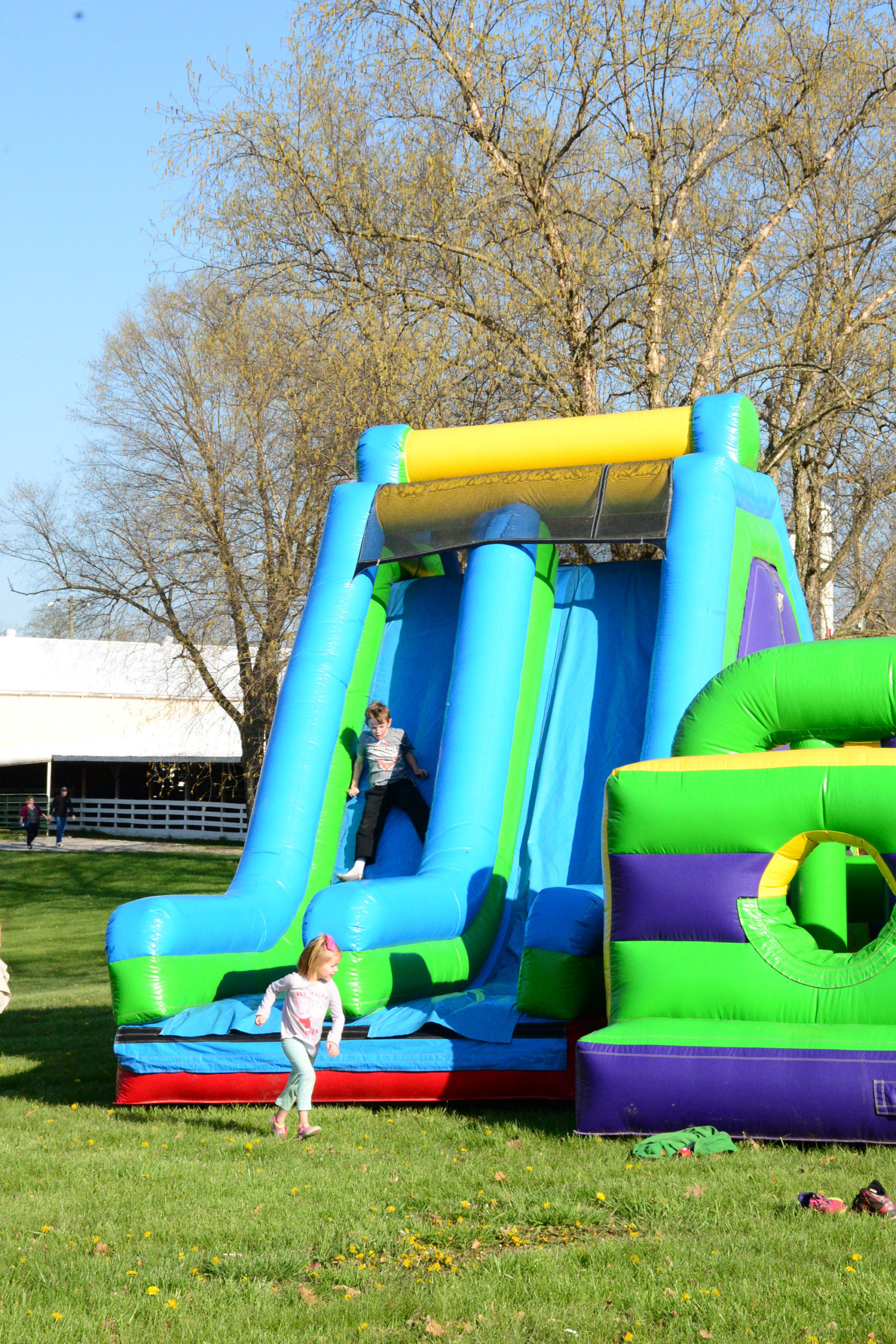 A colorful inflatable bouncy house with children playing on it outside.