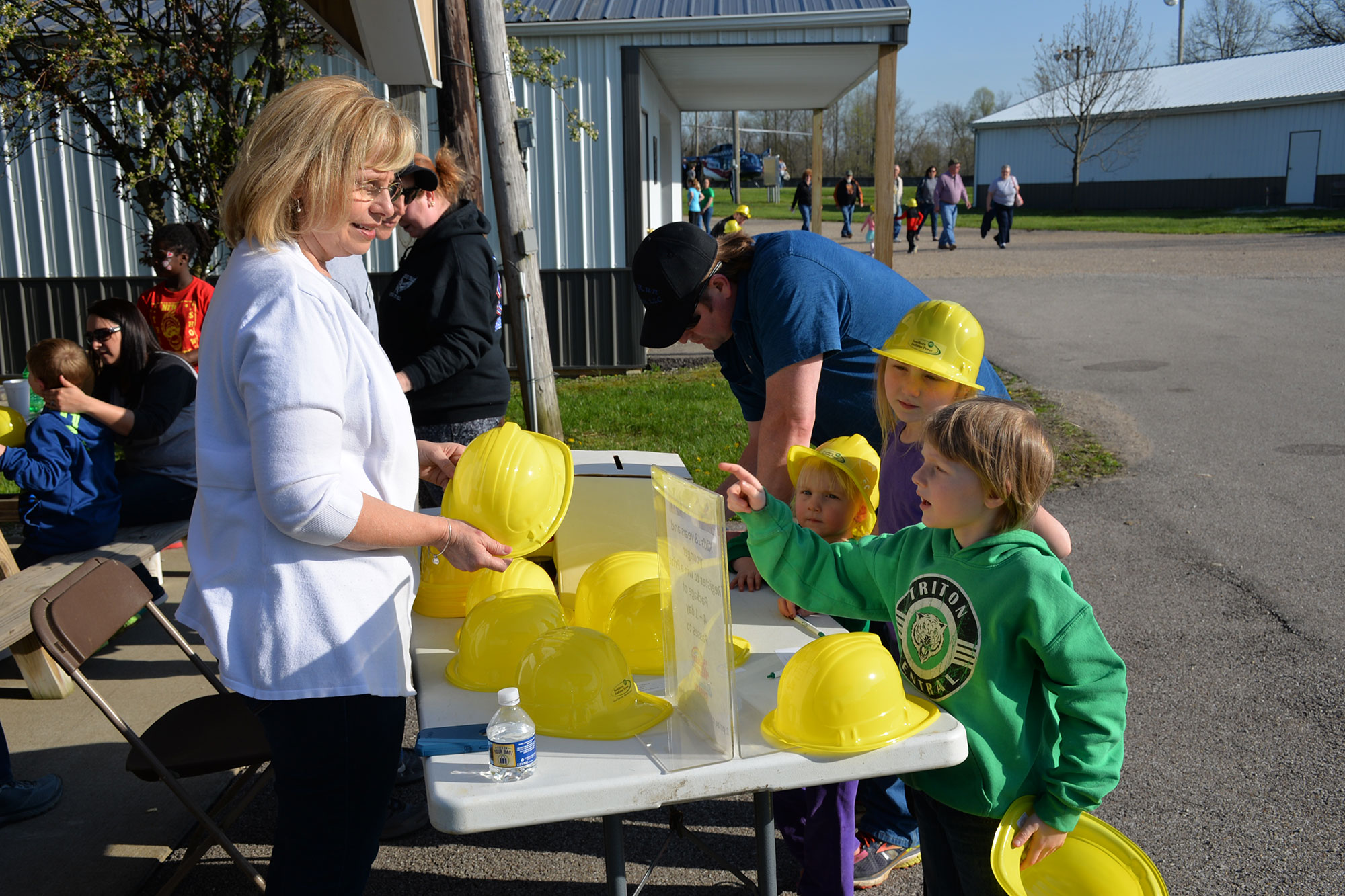 Woman handing out yellow plastic hard hats to young children.