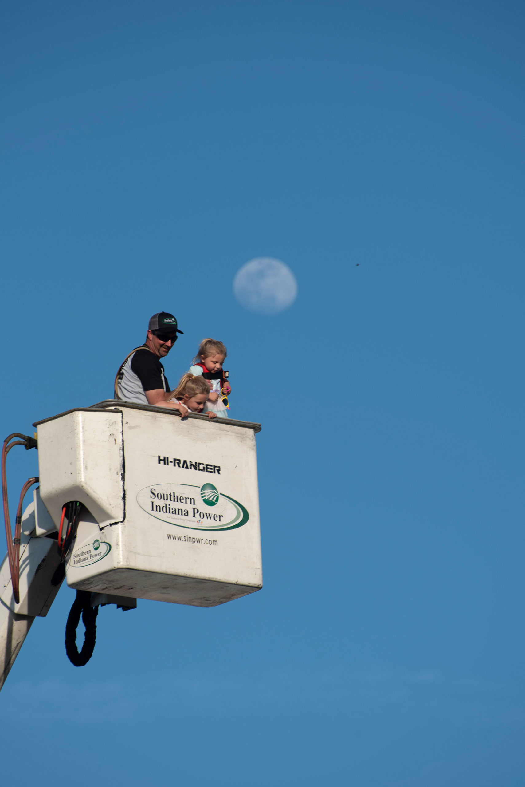 Lineman with two small children in bucket truck high in the sky.