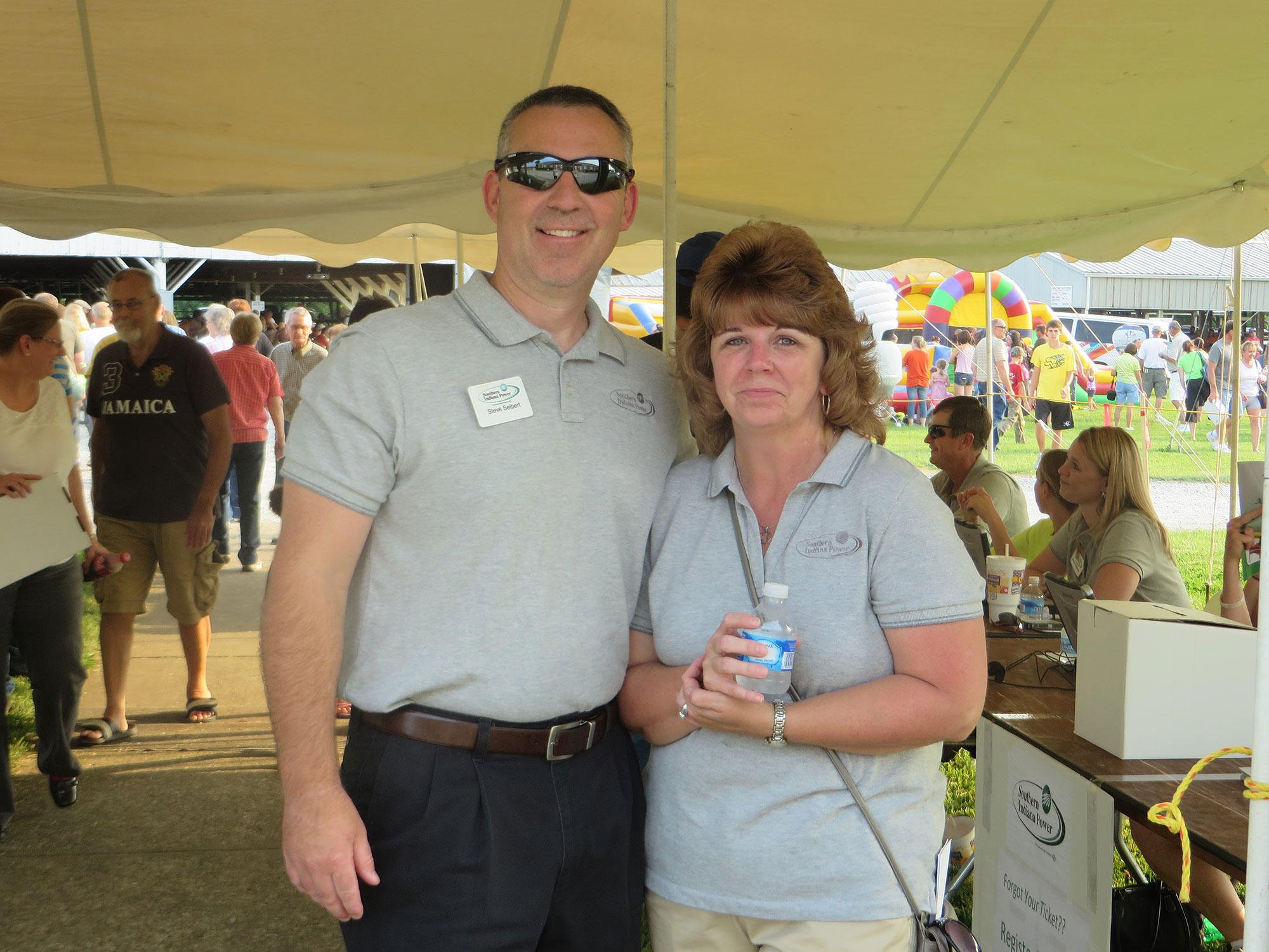 Two Southern Indiana Power employees together under a tent outside.