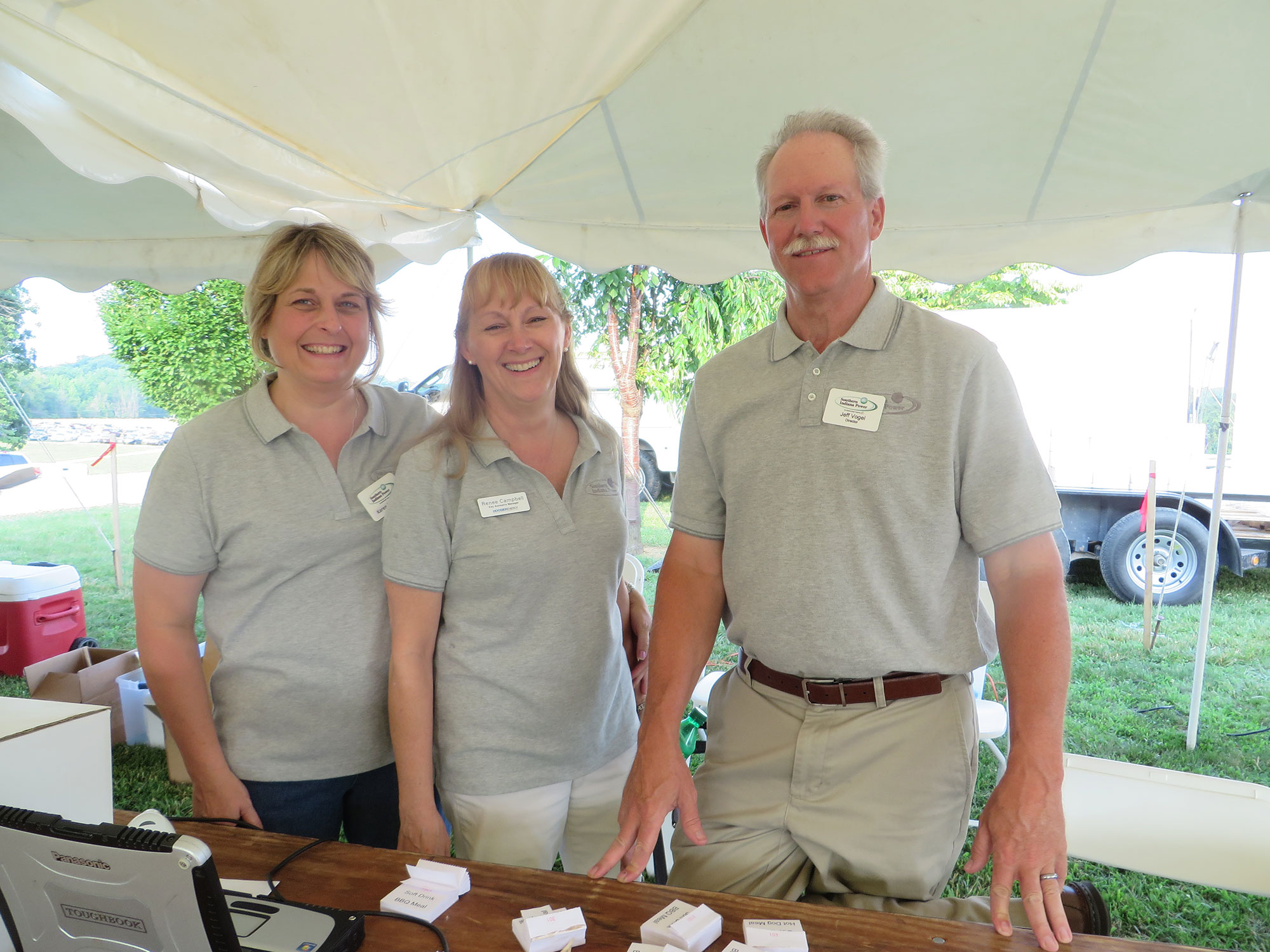 Three Southern Indiana Power employees under a tent outside.