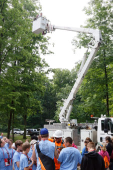 Lineman in box truck, with group of kids below.