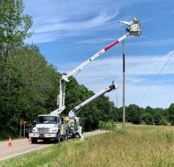 Lineman in a bucket truck working on power lines on a road lined with trees.