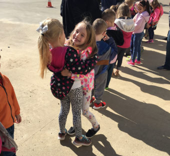 Two young girls hugging while standing in line outside with other children.