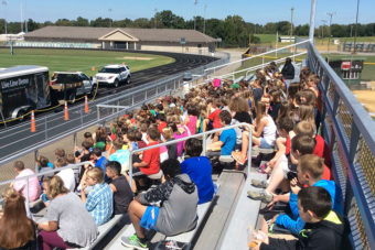 Large group of young children sitting on bleachers outside.