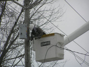 Lineman in bucket truck working on power pole during a snowstorm.
