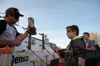 Lineman showing a glove to a young boy during demonstration.