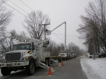 Lineman working on power lines on a road with snow on the ground.