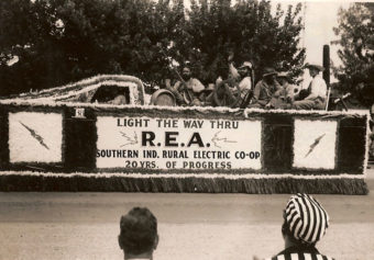 """A black and white photo of a parade float with the sign """"Light the way thru R.E.A. Southern Ind. Rural Electric Co-op 20 yrs. of progress"""""""