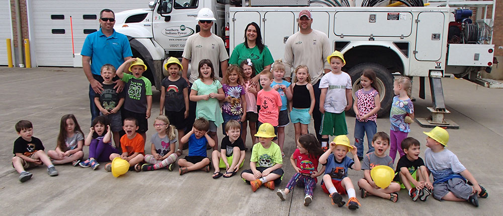 Large group of preschool children wearing hard hats with linemen in front of an electric truck.