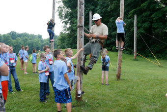 Lineman and young kids using safety harnesses to climb small poles.