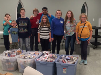 Group of kids with large filled bins.